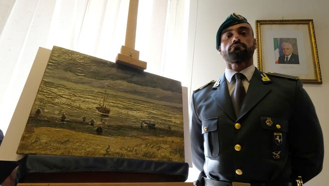 """An Italian border policeman stands next to """"Seascape At Scheveningen,"""" one of the two Van Gogh paintings stolen in Amsterdam 14 years ago that was recently recovered by organized crime investigators in Italy on Sept. 30, 2016."""