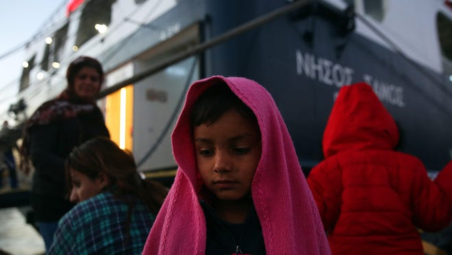 Refugees wait for transport after they arrived on the ferry 'Nissos Samos' from Lesvos island at the port of Piraeus, Greece, on Dec. 11, 2017. The ship arrived at the port carrying 265 refugees and migrants, who will be distributed to several hosting centers across the region of Athens.