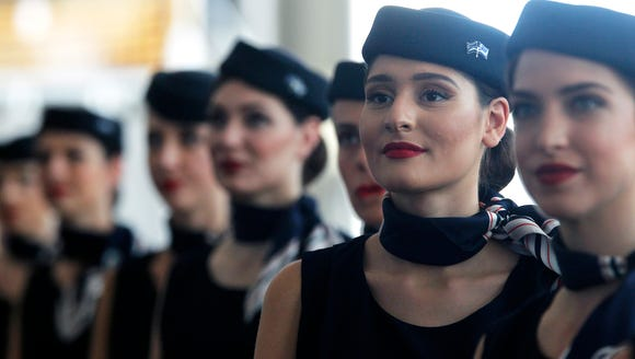 Aegean Airlines flight attendants look on during a