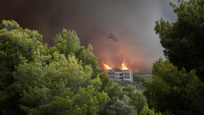 A firefighting helicopter flies over a building during a forest fire in Neo Voutsa, a northeast suburb of Athens, Greece, on Monday. After the wildfire in Kineta a second wildfire broke out in the Penteli Mountain. Two major forest fires were raging out of control on either side of the Greek capital Monday, burning houses, prompting residents to flee and turning the sky over Athens a hazy orange from the smoke.  EPA-EFE/ALEXANDROS VLACHOS ORG XMIT: YAN04