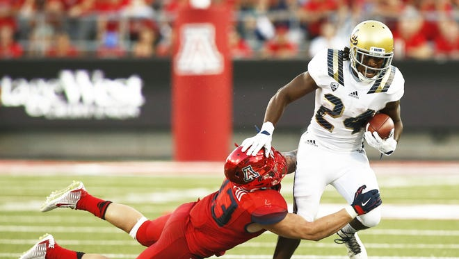 UCLA's Paul Perkins (24) escapes the tackle by Arizona's Scooby Wright III in the first half of Saturday's game in Tucson.