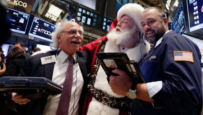 Traders pose with Santa on the floor of the New York Stock Exchange in 2014.