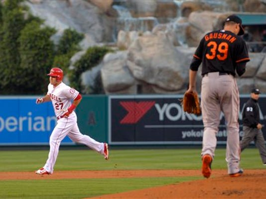 Los Angeles'' Mike Trout, left, rounds second after hitting a solo home run as Baltimore pitcher Kevin Gausman walks back to the mound during the first inning on Friday in Anaheim, California.   Summary