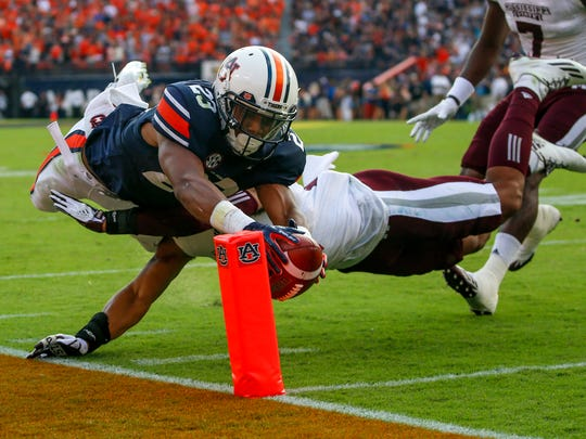 Auburn wide receiver Ryan Davis (23) dives past Mississippi State defensive back Johnathan Abram (38) into the end zone for a touchdown during the first half of an NCAA college football game Saturday, Sept. 30, 2017, in Auburn, Ala. (AP Photo/Butch Dill)