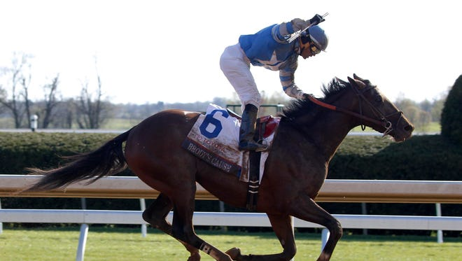 Jockey Luis Saez celebrates aboard Brody's Cause as he crosses the finish line to win the Blue Grass Stakes at Keeneland.