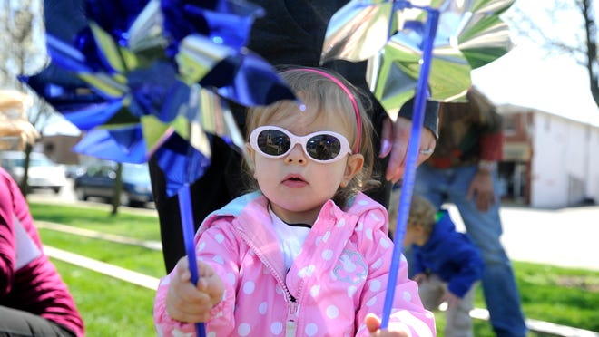 Maddux Diehll, 2, gets ready to plant a pinwheel during the Pinwheels for Prevention event at Yoctangee Park on Saturday with her mother, Michelle Diehl who works for Ross County Children's Services. 1,216 pinwheels were planted near the entrance of Yoctangee Park on Saturday to mark every report of child abuse and neglect in Ross County in 2014. The annual event, Pinwheels for Prevention, was led by Julie Oates of the Child Protection Center. The Child Protection Center can be reached at (740)779-7431 or online at www.thechildprotectioncenter.org or you can contact the Ross County Children's Services at (740) 702-4453.