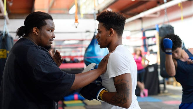 Antwoine Dorm Sr. demonstrates the importance of moving a certain way to perform a move with Josiah Okehie, 18, of Springettsbury Township, at Stick-N-Move Boxing in York Thursday, June 11, 2015. Antwoine Dorm Sr. runs the youth boxing gym, fulfilling a father role for many of the kids, some of whom don't have their own fathers in their lives.