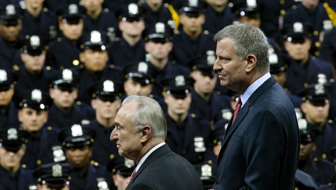 New York City Mayor Bill de Blasio, right, and NYPD police commissioner Bill Bratton, center, stand on stage during a New York Police Academy graduation ceremony, Monday, at Madison Square Garden in New York City.