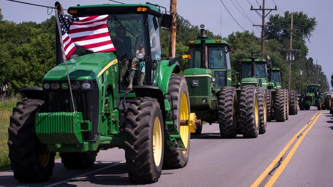 Tractors lead a procession out of Rothfuss Park in Penfield on Saturday after the funeral service of longtime town resident Terry Rothfuss.