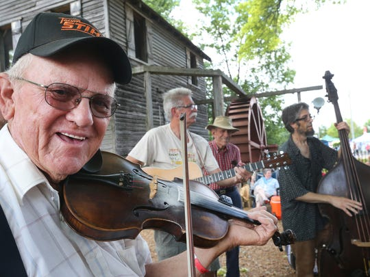 Billy Hazelwood, left, Mike Singleton and Samuel Louis Morgan play during a jam session next to the Mill at Cannonsburgh Village at the 39th Annual Uncle Dave Macon Days Festival on July 9, 2016.