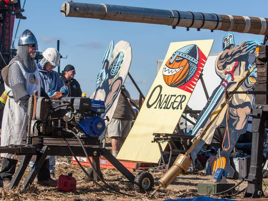 Onager team captain Bob Carbo charges the team's torsion machine as they prepare to launch at Punkin Chunkin in Bridgeville in 2013.