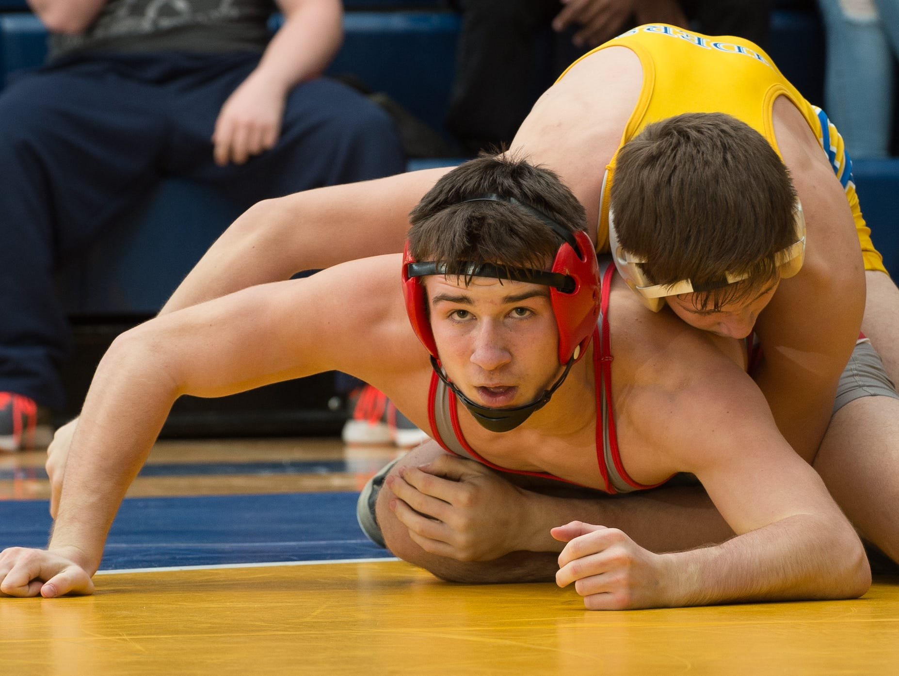 Smyrna's Greg Baum looks to his coaches for instructions while wrestling Caesar Rodney's Jackson Dean in the 132 pound championship match at the Henlopen Conference wrestling tournament at Sussex Central High School.
