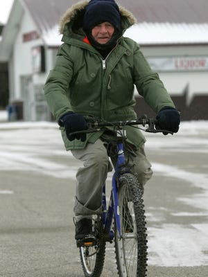 A bundled-up Leo Larson rides his bicycle for a trip to the pharmacy in Evansdale in frigid weather that gripped the state on Monday.