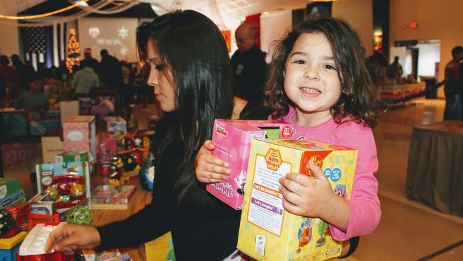 In this photo, a young child clings to her toys she selected at this year's Otero County Toys for Tots program at the Sgt. Willie Estrada Civic Center Friday, Dec. 23.
