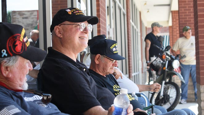 Vietnam veterans, from left, Larry Stoneking, Dan Hellmuth and John Kahne sit outside a military recruitment center in Middletown Wednesday. The veterans said they were carrying concealed weapons to protect the personnel inside, who are not permitted to do so.