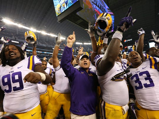 LSU coach Les Miles and his team celebrate a win against Texas Christian at AT&T Stadium. The Tigers beat the Horned Frogs 37-27.