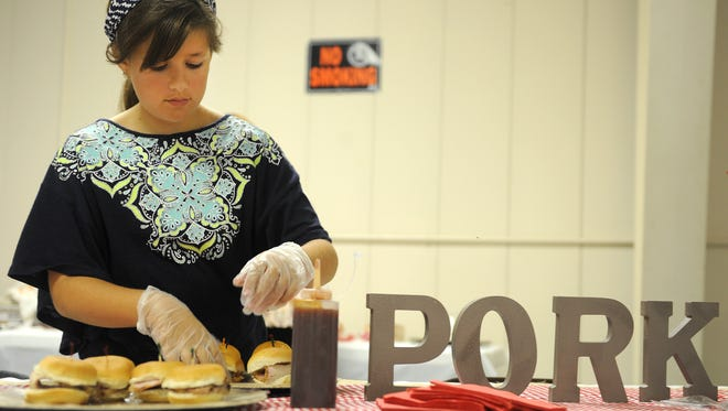 Ashley Davis, from Hord Livestock, displays freshly made pork loin sandwiches during the Taste of Crawford County event last summer at the Crawford County Fairgrounds.