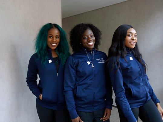 Members of the Nigerian women's bobsled team, from left, Akuoma Omeoga, Seun Adigun and Ngozi Onwumere, pose for a photograph during an interview with The Associated Press at the 2018 Winter Olympics in Pyeongchang, South Korea, Tuesday, Feb. 13, 2018. Despite being American born, Nigeria's first-ever bobsled team says they're representing the culture they were raised in.   (AP Photo/Patrick Semansky)