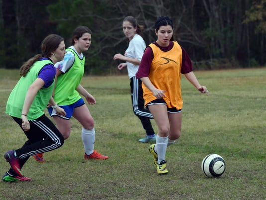 Aleeza Still (far right), a senior on the Pineville High School girls' soccer team, practices Thursday with the rest of the team.