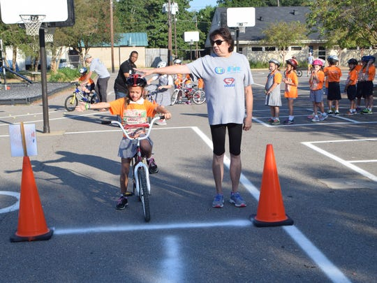 Pat Ryder (right) of Fit Families for Cenla teaches Haley Bridges Carson Callahan (left), a third-grader at Our Lady of Prompt Succor, proper bicycling turn signals at a bike safety clinic at the school Wednesday.