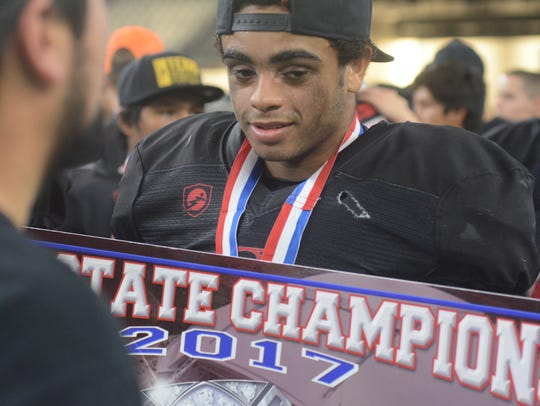 Strawn tight end/defensive back Zavion Winegeart walks around with a state championship poster after the Greyhounds' 78-42 win over Balmorhea in the Class 1A Division II state championship game Wednesday at AT&T Stadium in Arlington.