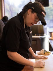 Meghan Scullion prepares an order during a post-lunch rush at the Pita Pit in downtown East Lansing on Wednesday, Oct. 12, 2016. Scullion said economic inequality is one of the social issues that draws her to the Democratic Party, but she doesn't think Hillary Clinton is anything special.