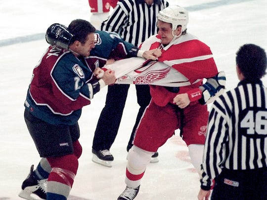 Claude Lemieux of the Colorado Avalanche and Darren McCarty of the Detroit Red Wings mix it up in March 1997. The teams' historic rivalry will be replayed Friday during an outdoor match in Denver.