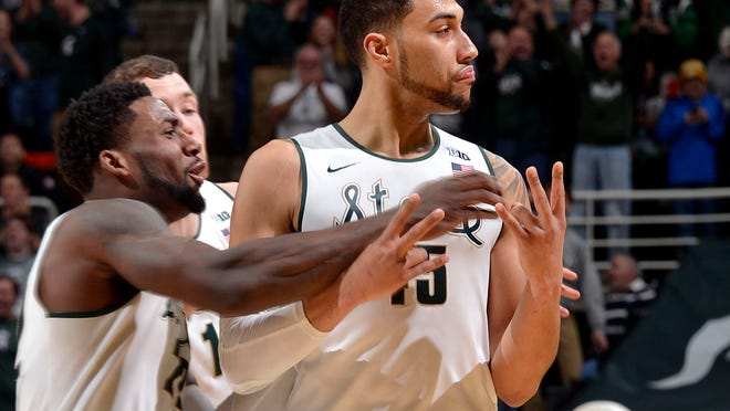 Teammates mob Denzel Valentine after his game-winning three-point shot as MSU beats Ohio State, 59-56, Saturday afternoon at Breslin Center in East Lansing.