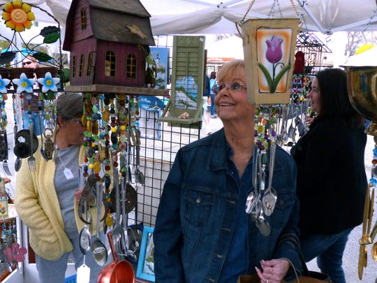 The 28th Annual Riverwalk Arts Festival will take place Saturday and Sunday in downtown Milton. In this photo from a previous Riverwalk Arts Festival, Lois Finch checks out the unique wind chimes made from recycled materials at the Best of Chimes booth of Brent and Tabatha Blackburn.