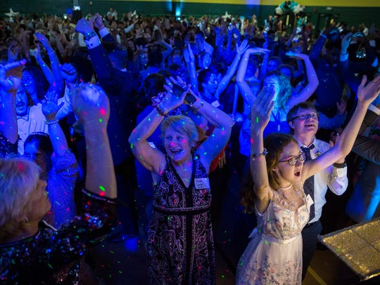 The crowd puts their hands in the air during YMCA at