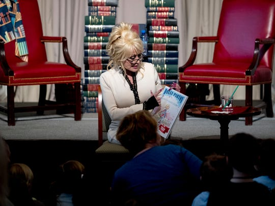 "Singer-songwriter Dolly Parton reads her book ""Coat of Many Colors"" to children during an an event where her organization Imagination Library donates it as the 100 millionth book to the Library of Congress collection, Tuesday, Feb. 27, 2018 in Washington. The Library of Congress and Imagination Library also announce a story time for children on the last Friday of each month in the Great Hall of the Thomas Jefferson Building from March through August. (AP Photo/Andrew Harnik)"