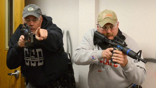 Tim Johnson, of the Brown County sheriff's Office, left, and John Peters, of the Green Bay Police Department, take part in an active shooter training exercise at the former Packerland meat packing plant, Thursday, October 30, 2014.