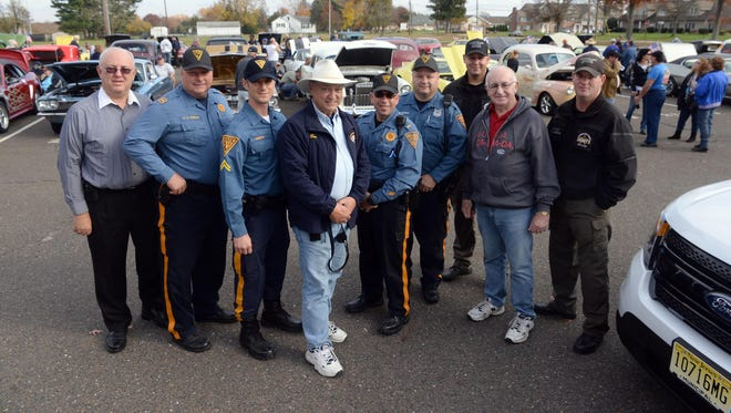 Members of Vineland Police, NJ State Police, and Cumberland County Sheriff pose for a photo with event organizer Ben Notaro, of Vineland (center), during the Blue Cruise car show, Sunday, Nov. 1, in Vineland.