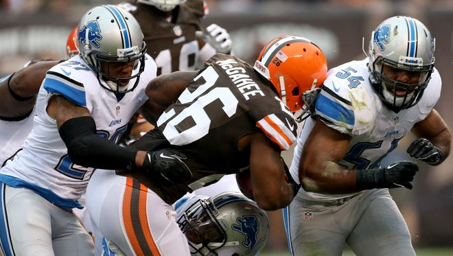 Detroit Lions safety Glover Quin and linebacker DeAndre Levy, right, tackle the Cleveland Browns' Willis McGahee on Oct. 3, 2013.