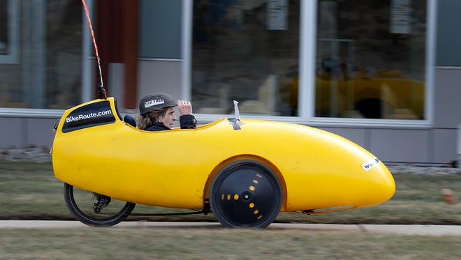 Martin Krieg cruises down the sidewalk on West Washington Street in his yellow Velomobile. Krieg is also a big fan of riding his velomobile on the Culture Trail and Monon Trail. He is also the director of the National Bicycle Greenway, a coast-to-coast bicycle highway. The velomobile s a human-powered vehicle enclosed for aerodynamic advantage and protection from weather and collisions.