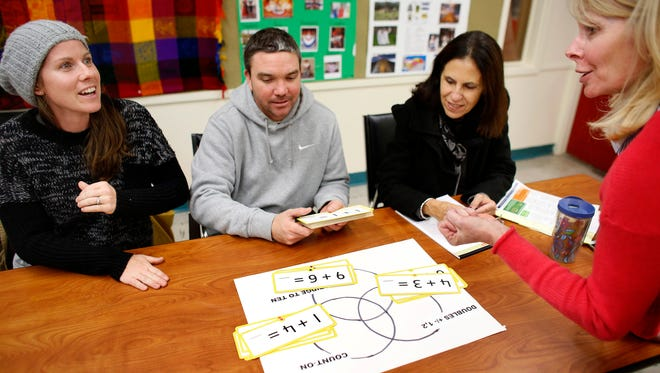 Parents Kate Ezyk, left, and her husband Matt Ezyk, second from right, both of Westerly, Mass., practice Common Core math techniques with elementary school principle Polly Gillie, right. Nevada's partial Common Core test results show the state's students lagging in math.