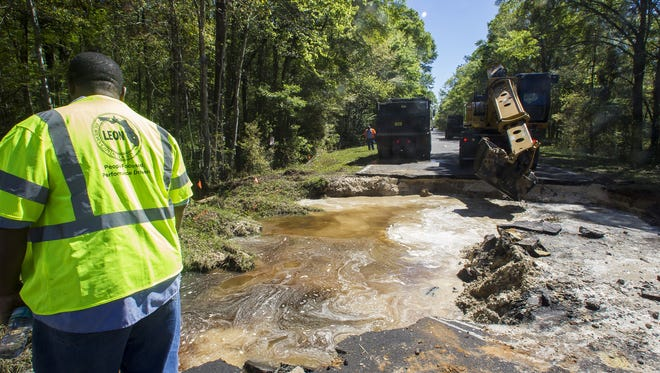 Leon County crews work to drain water flowing from St. Mark's river above a washed out portion of Tram Rd on Monday. Crew members suspect that the 4 1/2 inches of weekend rain resulted in the road's collapse.