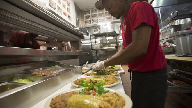 """Lead trainer, Deon Fellows preps plates of  """"Chicka Chicka Boom Boom"""", a chicken enchilada dish and house favorite at Chuy's Restaurant. The Tex-Mex restaurant located on 904 E. Lafayette St is set to open on May 10, 2016."""