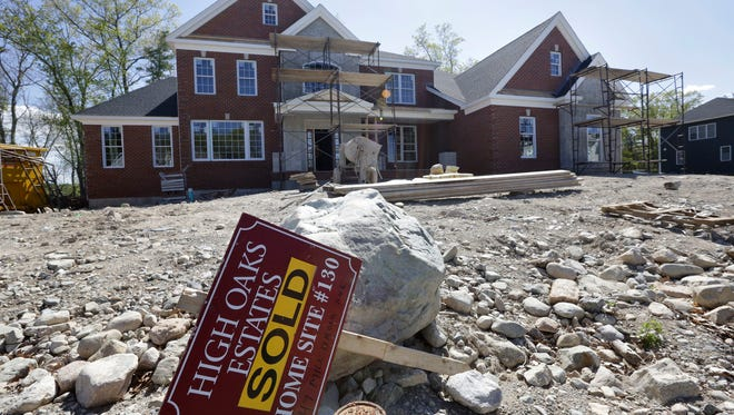 "In this Wednesday, May 18, 2016, file photo, a ""Sold"" sign rests in front of a house under construction, in Walpole, Mass. On Thursday, June 22, 2016, 2016, the Commerce Department reports on sales of new homes in May."