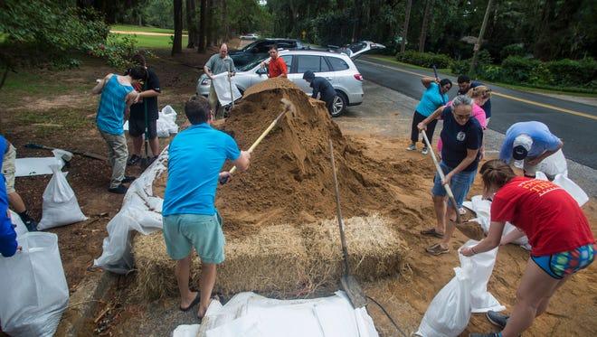 File art of people filling sandbags in Tallahassee before Hurricane Hermine.
