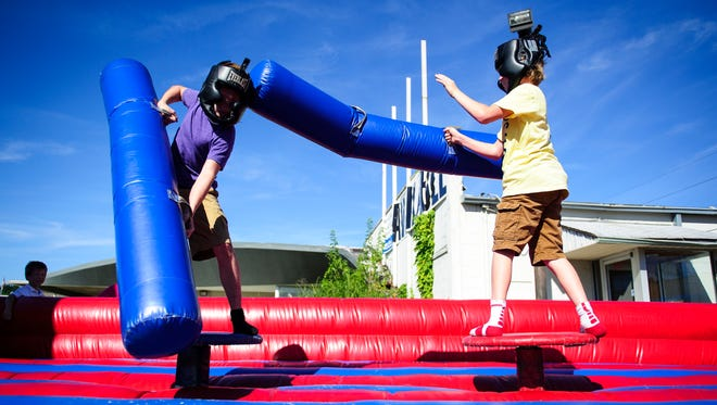 David Wesley Boyer (left), 16, and Kaleb Fitzpatrick, 13, play in the inflatable jousting arena at the Holly's House Fun Fair in 2013.