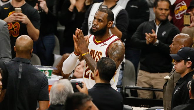 Cleveland Cavaliers small forward LeBron James celebrates after scoring his 30,000 career point during a time out against the San Antonio Spurs at AT&T Center.