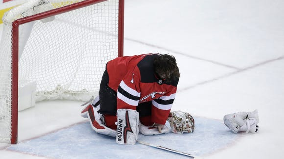 New Jersey Devils goalie Keith Kinkaid is slow to get up after taking a hit during the third period of the team's NHL hockey game against the Pittsburgh Penguins, Saturday, Feb. 3, 2018, in Newark, N.J. The Devils won 3-1. (AP Photo/Julio Cortez)