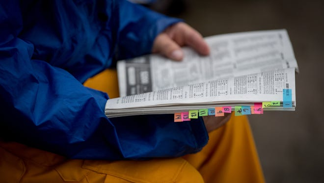A man carefully reviews the odds before placing his bet on Kentucky Derby Day in Louisville, Kentucky, Friday, May 5, 2018
