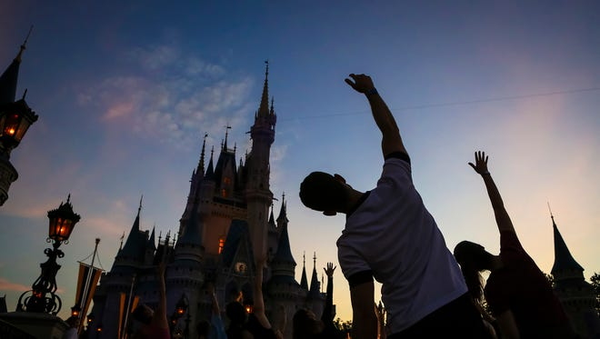 In this Thursday morning, June 21, 2018 photo, more than a thousand Disney cast members do yoga in front of Cinderella's Castle at the Magic Kingdom as the sun rises on International Yoga Day at the theme park in Lake Buena Vista, Fla. (Jacob Langston/Orlando Sentinel via AP)