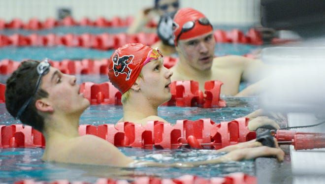 Winner John Acevedo of Waukesha South / Catholic Memorial (center) and Michael Linnihan of Brookfield Central / East (left) check out the scoreboard at the end of the 200 freestyle Saturday.