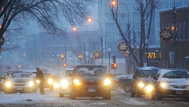 As fresh snow falls, a man clears his windshield along Main Avenue near its intersection with West 10th Street during Monday's snowfall, Dec. 28, 2015, in Sioux Falls.