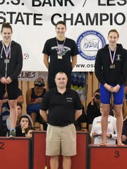 West Salem senior Mackenzie Rumrill (center) stands on the medal stand after winning the state championship in the 100 butterfly. At front is West Salem coach Dan Evans, at left is Clackamas' Laine Visscher and at right is Century's Sara Metzsch.