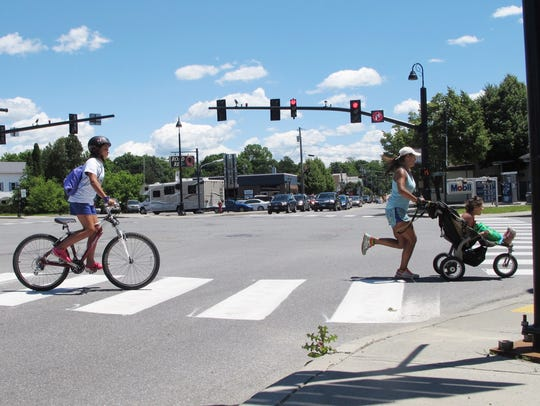 Lily Boutin, 11, at left, bicycles across Five Corners
