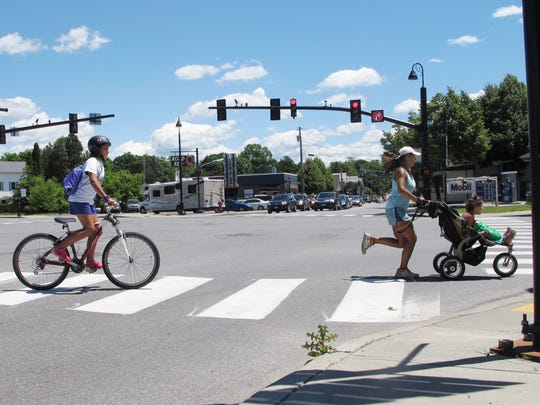 """Lily Boutin, 11, at left, bicycles across Five Corners in Essex, in the company of her mother, Courtney Boutin, and sister, Isabella Boutin, 6. Motorist (and pedestrian) wait-times at the intersection are expected to shorten next year with the completion of the """"Crescent Connector"""" bypass. Photographed on Thursday, June 23, 2016."""